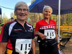 Kaksi hymyilevää naista seisoo suunnistuskilpailun maalissa suorituksen jälkeen.